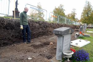 Anders Edvinsson tittar ned på det framgrävda skelettet som tros vara omkring 900 år gammalt. Bilden är från början av september när utgrävningen nyss hade påbörjats. Då hade de bara hittat 14 skelett.