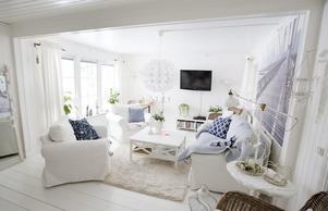 Vardagsrummet. Vardagsrummet går i vitt med blått som accentfärg på kuddarna. En tavla täcker en stor del av ena väggen och de fönstrena ger rejält med ljusinsläpp.