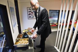 Dukar upp. Bilhandlaren Olle Mellinger fixar med julmaten samtidigt som företagets anställda hugger in på godsakerna.