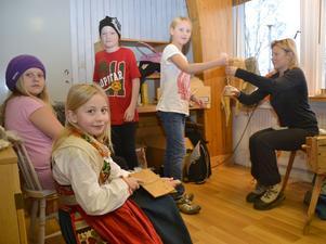 Täpp Kerstin Arnesson provar på att karda ull och mamma Anna Arnesson hjälper Hannah Siwert att spinna på slända.