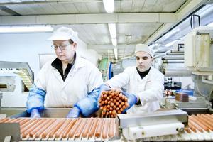 Lena Forsberg och Wasim Abdulmula förpackar 70-grams  godingar till korvkioskar.