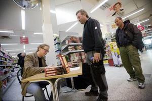 """Författaren Jonas Moström skriver hälsningar och autografer på  löpande band. Joakim Sjöberg har fått en beställning hemifrån  på boken """"Evig eld"""". Jens Granbom får snällt vänta på sin tur."""