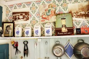 Så här vill han ha det i köket: kryddhyllan, durkslagen, handvirkade grytlappar och pärlspontpå väggen – fast tapeten