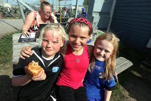 GLADA MINER. Signe Backlund, Amanda Sjölander och Hanna Eriksson njuter av vårsol och bullar under den stora, årliga fotbollsturneringen för Sandvikens skolor.