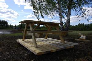 Bänkbord med trägolv. Ett mysigt utflyktsmål, som det nu lätt går att nå via långbryggan, som utgår från Mossbäck i bakgrunden.