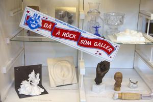 Högt och lågt. På en monter med konstföremål sitter en klisterlapp från Rotebergs-raggarns fanclub.