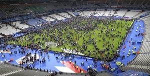 Åskådarna till fotbollsmatchen mellan Frankrike och Tyskland samlas på Stade de Frances plan efter fredagens terrorattack.