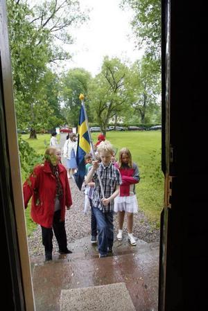 Till slut ringer klockorna och eleverna får lämna regnet utanför och tåga in i kyrkan.