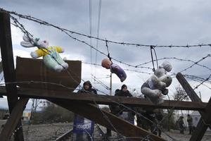 Dockor och gosedjur hänger i taggtråden på gränsen mellan Grekland och Makedonien.