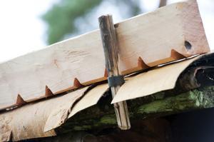 Från början var det näver i flera lager som täckte visthusbodens tak. Varje taksida förses även nu med näver, men bara längst ned mot ytterkanten för att ge det rätta intrycket av hur huset en gång såg ut.
