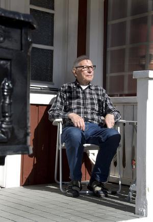 När stormen viner runt husknuten njuter Arne Carlsson av vårsolen på verandan.