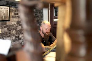 Tomas sitter och tecknar i sin studio.
