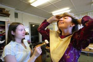 Erika Othzén är beredd att ge en hjälpande hand när Johanna Augutis ska sätta på sig peruken.