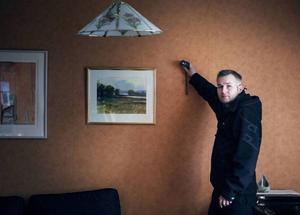 Anders Östergren mäter upp ett vardagsrum inför en golvslipning.