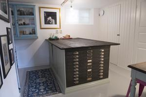 På nedervåningen finns arbetsrummet med en stor arbetsbänk med ett tidensligt inbyggt arkivskåp. Den persiska mattan ger en ombonad känsla som Doreen Månsson tycker om.