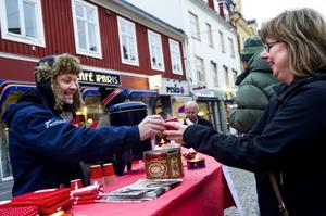 Thomas Nordberg från Svedjeholmskyrkan delar ut glögg till förbipasserande. Kristina Westerström tar emot.