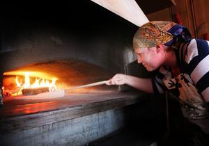Caroline Näsvall snurrar tunnbrödet så att det blir jämn gräddat. För att få färg på bröden krävs en perfekt låga i ugnen. Den stora baksterfjölen har Anders Jonsson i Bruksvallarna tillverkat.