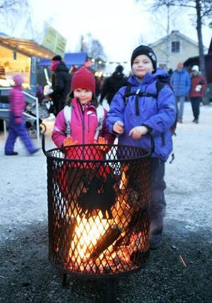 Syskonen Norna Frånberg, 4 år, och 6-årige Primus Frånberg från Björsjö värmde sig.