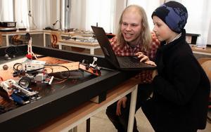 Programmering.  Fredrik Löfgren stöttar och Esaias Wide, 8 år, styr legoroboten som han har tänkt.