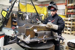 Zaher Ali Shaffa svetsar en redskapsdel till en grävmaskin. Han har jobbat hos Drivex i tre år och började i den gamla verkstaden först innan han för två år sedan kom till verkstadslokalen på Kullen.