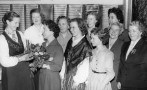 1958. Vävutställningen i Söderala succé. De nio kursdeltagarna tillsammans med sin lärarinna fröken Margit Skogens, Växbo som fick mottaga elevernas hjärtliga tack och (som synbarligt bevis) en vacker blomsterbukett. Damerna är fr. v. fru Ester Rönneseth, Heden, fru Majken Blom, Asta, lärarinnan, fröken Skogens, fru Gullan Svensson, Heden, fröken Karin Häger, Heden, fröken Kerstin Hagström, Orsta, fröken Ingegerd Larsson, Asta, fru Margareta Bäckman, Söderala (längst bak), fru Nanny Svensson, Söderhamn och fru Gerd Larsson, Söderhamn.