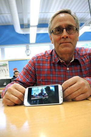 Läraren Lars Ljunggren streamar sändningen från klassrummet till sin mobiltelefon. Han ser därmed sig själv bli filmad samtidigt som han fotograferas av DT:s utsände.