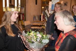 Arbogas 76:e lucia Emilia Norling uppvaktas med blommor av Lionspresidenten Täpp Birgitta Jonsson.
