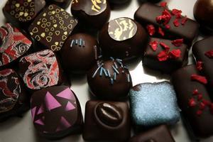 Chokladpralinerna är fyllda med tryffel med smak bland annat av blåbär, smultronchili, moccawhiskey och lakritsviol.Brytbitar choklad till kaffet och högklackat i choklad.
