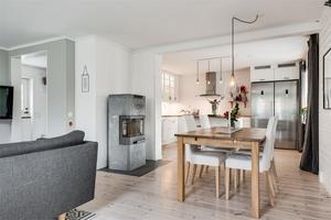 Från vardagsrummet ser man in till det vita köket i lantlig stil.