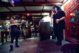 Kvällens karaokevärdinna bjuder själv på ett nummer. Stammisen Tina Dahlkvist dansar förtjust.