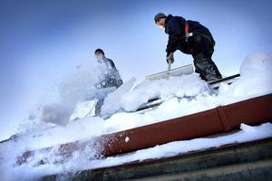 Just nu ligger det mängder av snö på stadens tak. Om den inte tas om hand är risken stor att någon ovetandes fotgängare får den över sig. På bilden syns Tommy Lindberg och Morgan Nilsson skotta snö från Centrumhusets tak.