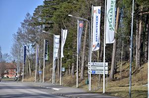 Välkommen. Flaggstänger med lokala företags flaggor satts upp för att göra vägen mer välkomnande.