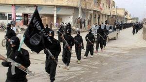 IS-krigare. Beväpnade män från Islamiska staten marscherar i staden Raqqa i Syrien.