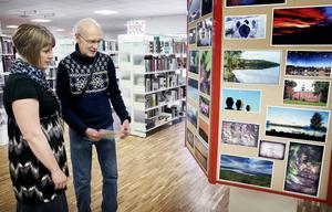 Bibliotekets Maria Morén diskuterar en del av bilderna på utställningen med Helge Henriksson.