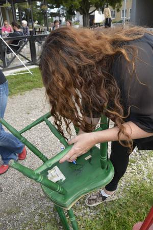 Dekoratör Ingela Lundwall signerar den stol som hon tagit med till restaurangen.