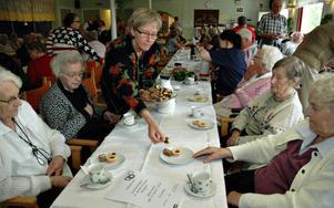 Äldreboendet Åsgården var specialinbjudna till kalaset. Eva Bäckvall, personal på Åsgården, lägger upp kakor till några av dem.           Foto: Sofia Wike