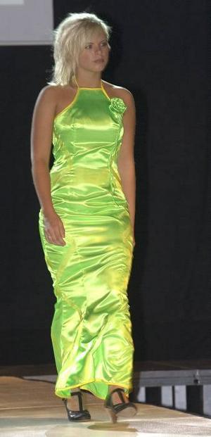Illgrön klänning som skulpturalt sytts efter kroppens former.