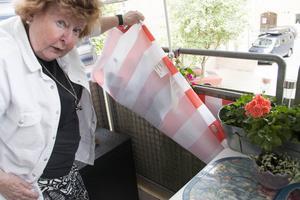 När Kerstin Hagstedt lyfter på det röd- och vitrandiga balkongskyddet är balkongen nästan svart av smuts.
