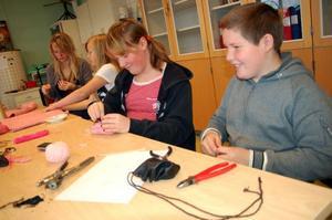 Emil Lundin skapar en amulettpåse av skinn att ha fiskegrejer i. Hans syster Emma Lundin syr ett mobilfodral. Bredvid henne Fanny Andersson och Märta Lööv.