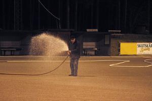 Lennart Holmgren vattnar grusbäggen på bandybanan innan isen ska läggas.