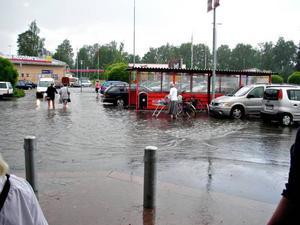 Folk på väg till sina bilar utanför Ica Maxi efter regnet.