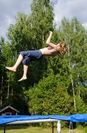 Agaton hoppar studsmatta på sommarstället. Foto: Mats Larsson