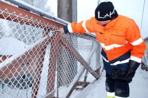 Per-Anders Fjellström pekar på ett av de fackverk som är ur funktion på Hängbron mellan Grönalid och centrala Vansbro.