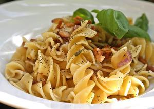 Stora pastaskruvar med kantareller och lök frästa i olivolja kryddas med färska örter och färskriven parmesanost innan de bjuds som inledning på den Medelhavsinspirerade måltiden.