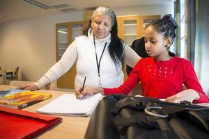 Språkläraren Reshan Berhe hjälper Mletetsega Guesh, som går i årskurs sju.