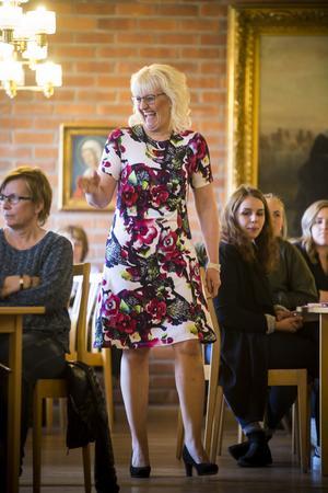 Helene Nilsson visar upp en somrig klänning, till den har hon svarta pumps.
