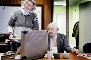 Anna-Lena Hellman från Studiefrämjandet hjälper 93-årige Birger Portström att visa gamla tidningsurklipp från den tiden då han drev en smedja på Öster. Nu har han varit med och skrivit en bok om sin kära stadsdel.
