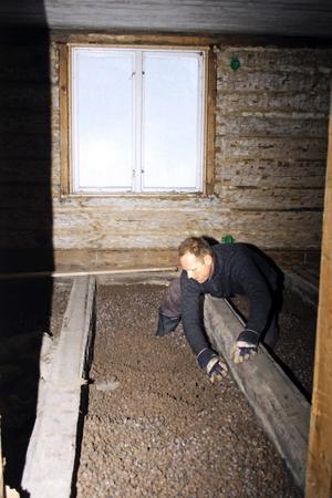 Frank Kerssens renoverar det andra huset på tomten, även det med originalträet från 1700-talet efter den tidens byggteknik. Här isoleras golvet med lerkulor. BILD: SAMUEL BORG