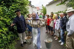 Under de tre dagarna hålls även vandringar genom fiskarstan med inslag av skådespel. Här är pigan på väg till grisarna med skulor.
