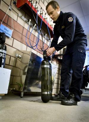 Brandkåren 2. Emil Bergström fyller på luft till rökdykarna.